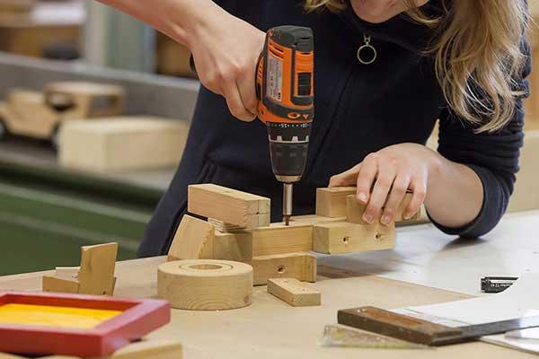 Mädchen in der Jugendwerkstatt lernt den Umgang mit Holz