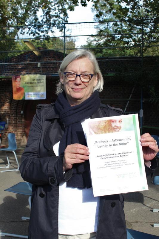 Foto: Dorothea Heiermann // Stadt Köln // Almut Gross (Geschäftsführerin Jugendhilfe Köln e.V.) mit der Auszeichnungsurkunde der UN-Dekade Biologische Vielfalt